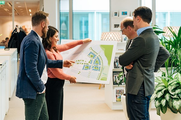 Four white collar workers looking at a site plan in the office.