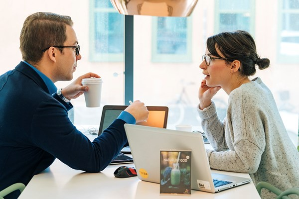 A white collar man and woman sitting down at the office over a cup of coffee to discuss a project.