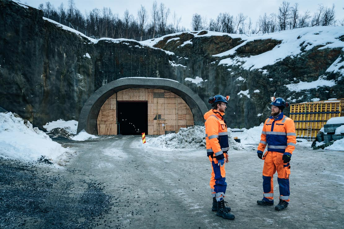 Two men working on The Sørkjosen Mountain Tunnel are standing outside the tunnel.